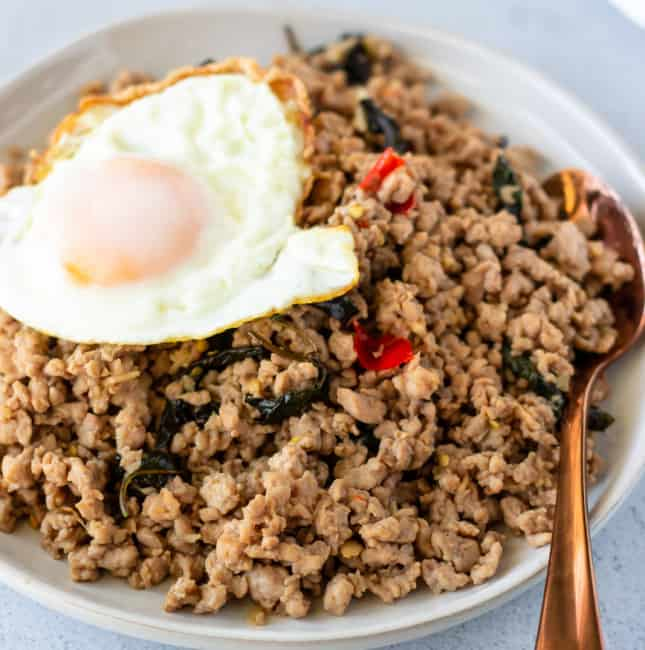 Ground pork stir fry on a white plate topped with a fried egg and bronze color spoon on the side.