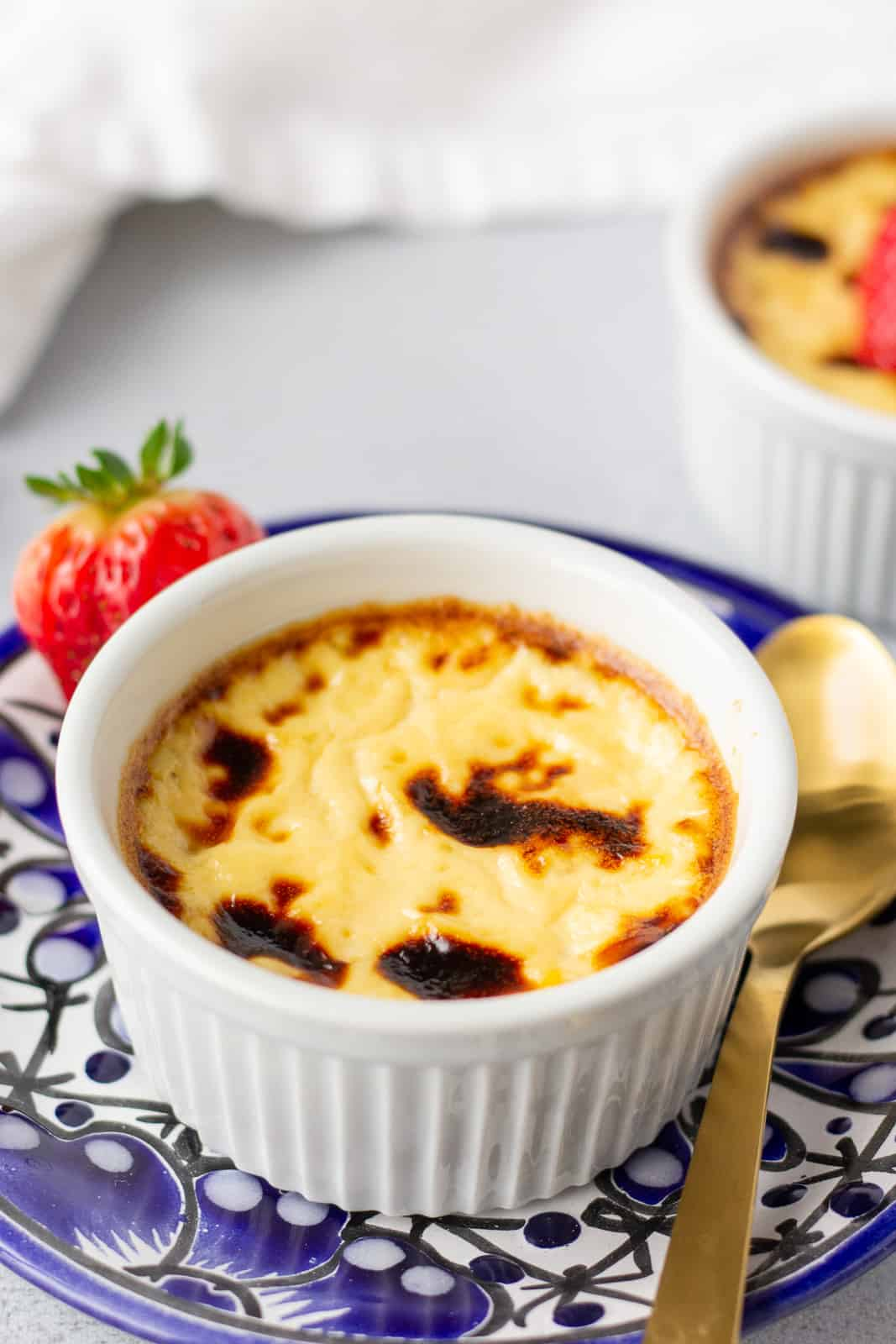 Jericalla in a white ramekin on a blue plate with a gold spoon on the side.