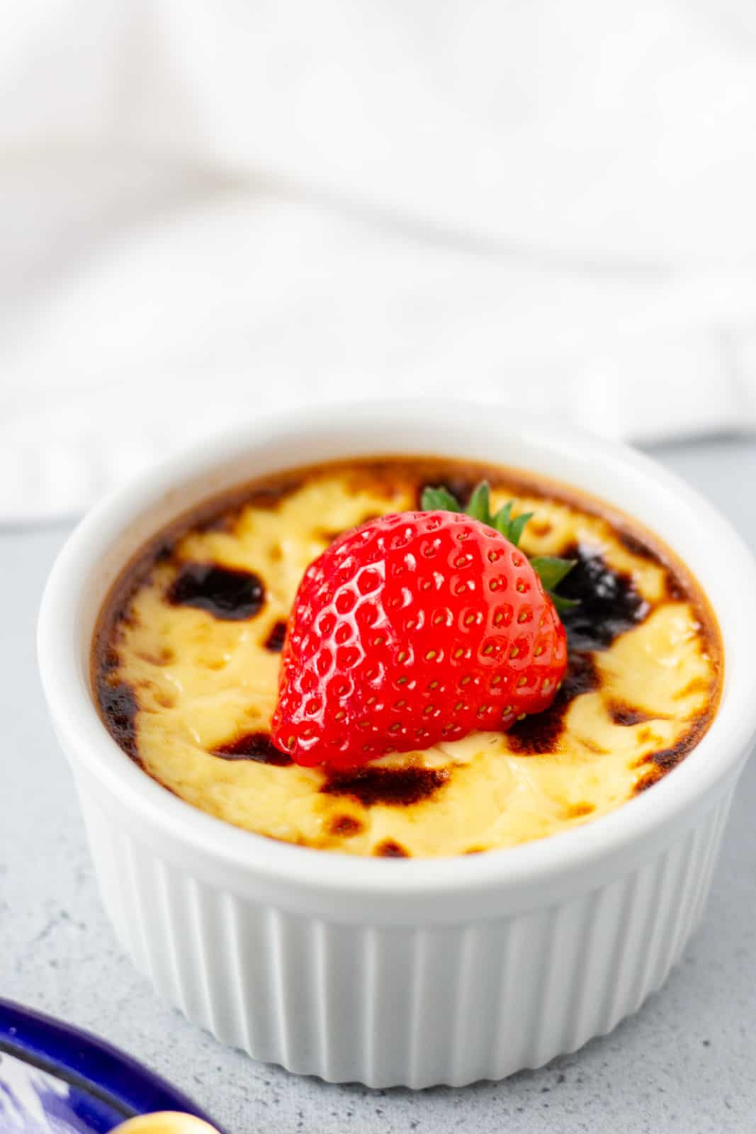 Single custard in a white ramekin with a strawberry on top.