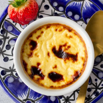 Overhead view of custard in a white ramekin on a blue plate with a gold spoon and strawberry garnish on the side.