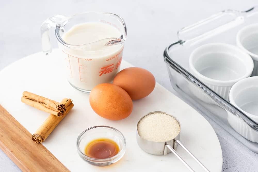 Ingredients on a marble board, milk, eggs, sugar, vanilla, and cinnamon.