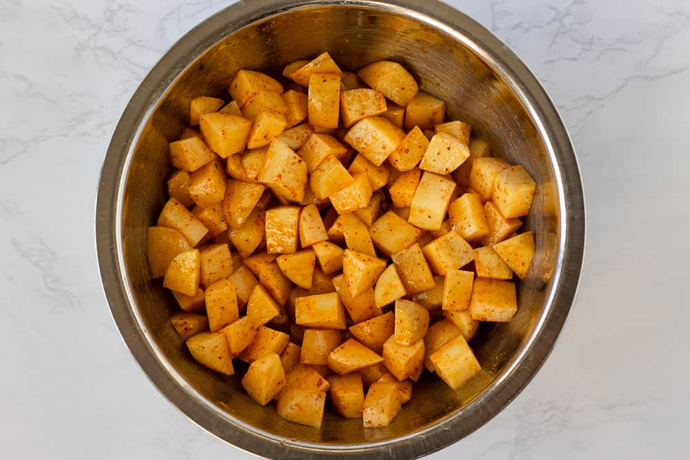 Diced potatoes in a silver bowl with seasoning.