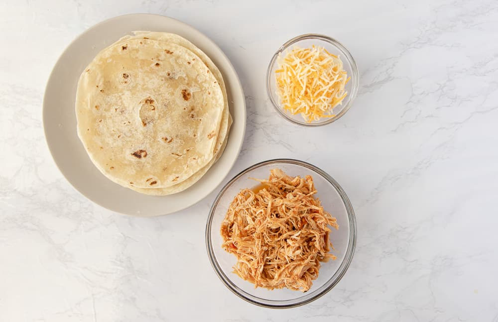 Overhead view of ingredients, flour tortillas, shredded salsa chicken, and mexican shredded cheese.