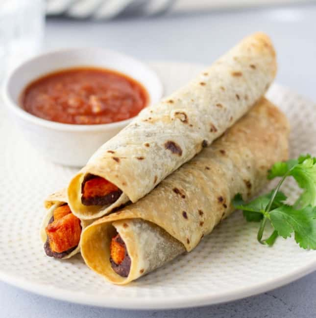 Up close view of 2 flautas on a plate with a side of salsa and a cilantro stem for garnish.
