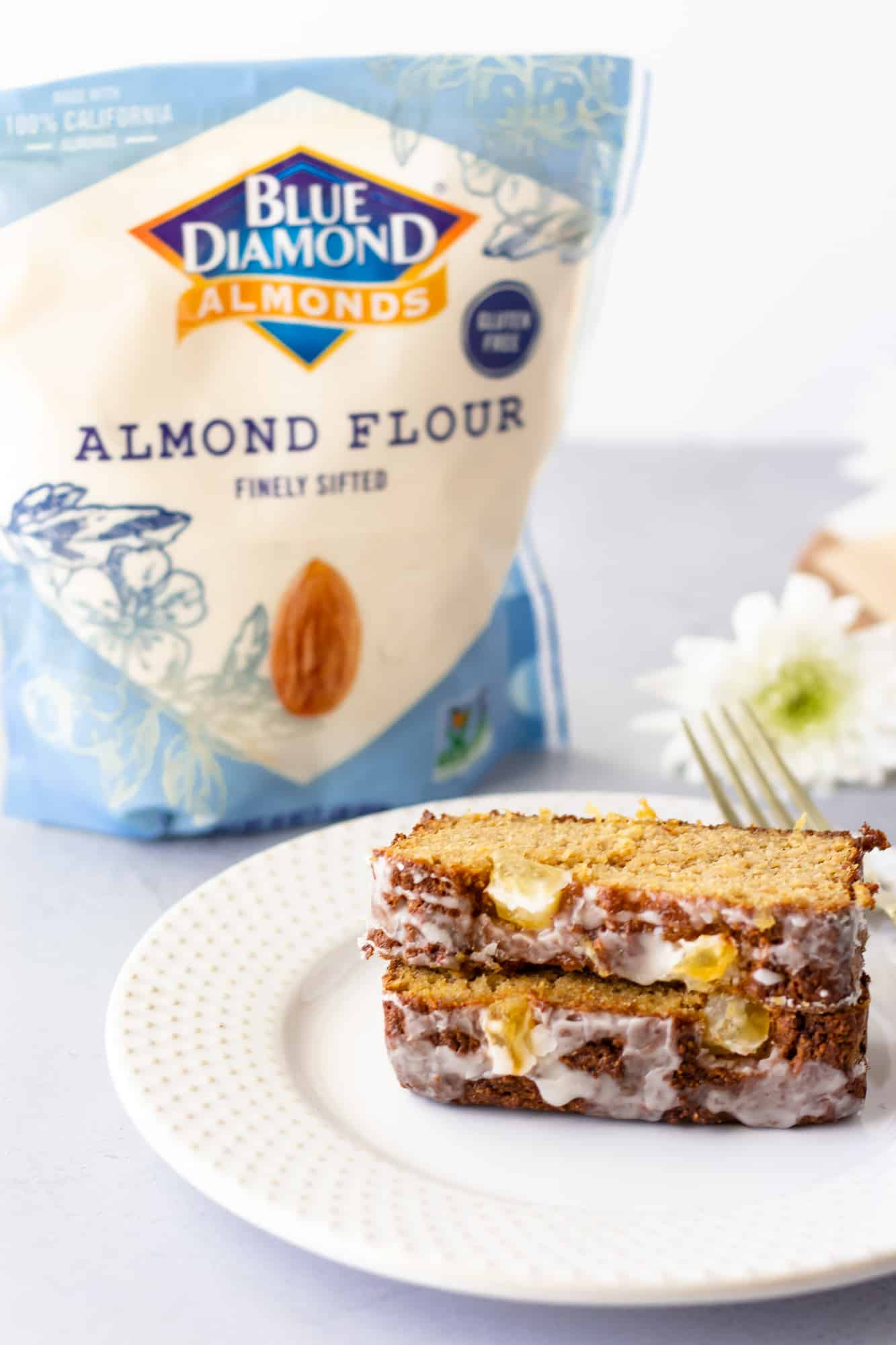 Two slices of pineapple cake on a plate with a bag of blue diamond flour in the background.