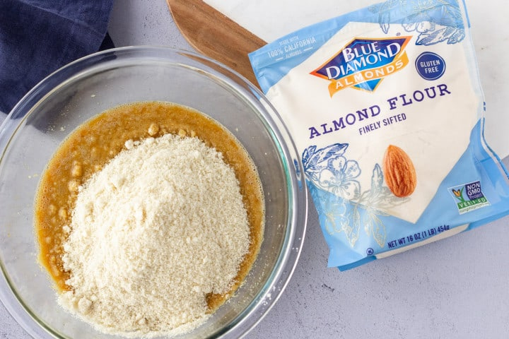 Batter in a glass bowl with almond flour poured on top and bag of Blue Diamond Almond Flour on the side.