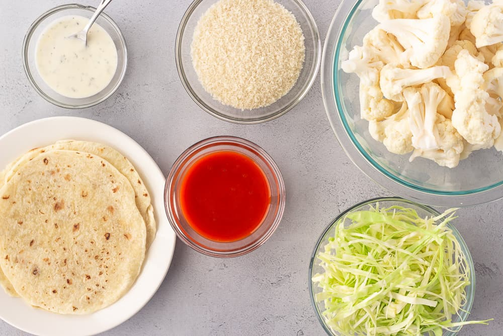 overhead view of ingredients, cauliflower, buffalo sauce, panko, cabbage, and tortillas.