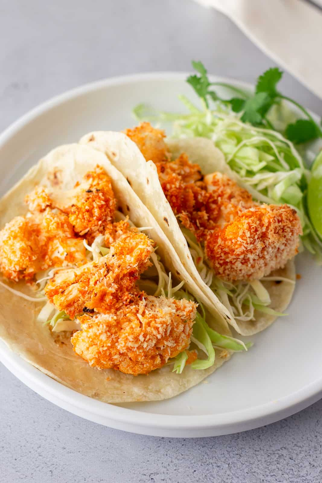 white plate with tortillas, shredded lettuce and panko buffalo cauliflower.