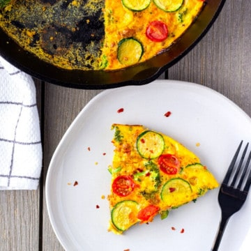 Slice of frittata on a plate with a large skillet on the side.