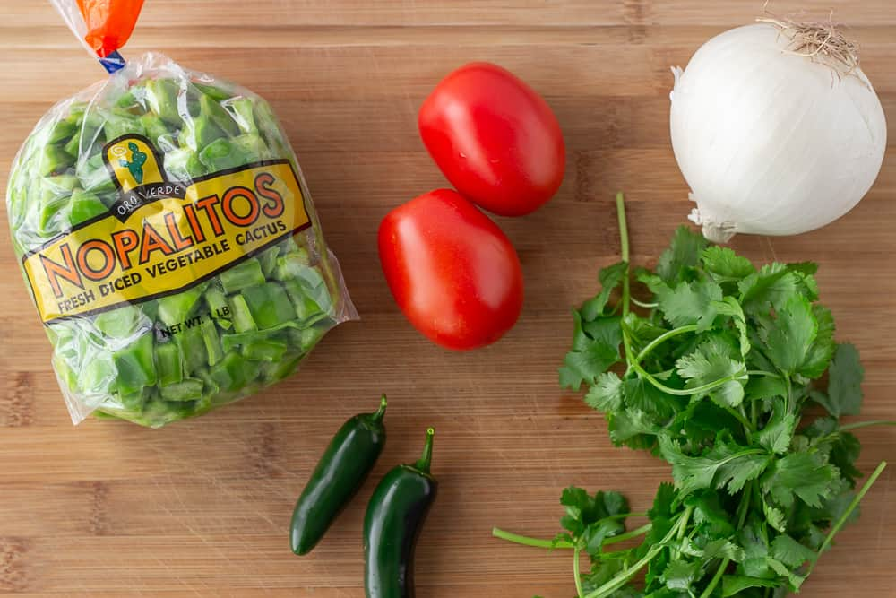 Ingredients on a cutting board, Nopalitos, roma tomatoes, white onion, cilantro, and jalapeno.