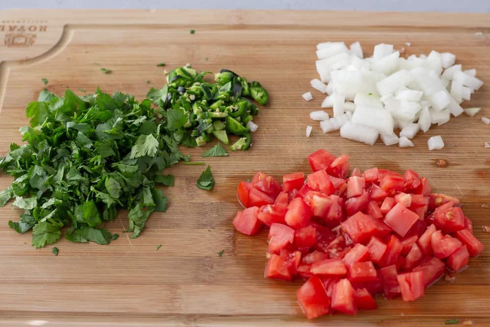 Cutting board with chopped tomato, onion, cilantro, and jalapeno.