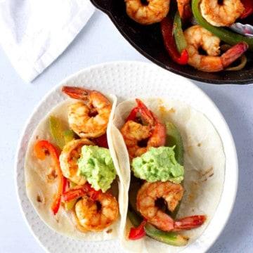 Two Shrimp Fajita tacos on Flour tortilla and a skillet of more shrimp on the side.