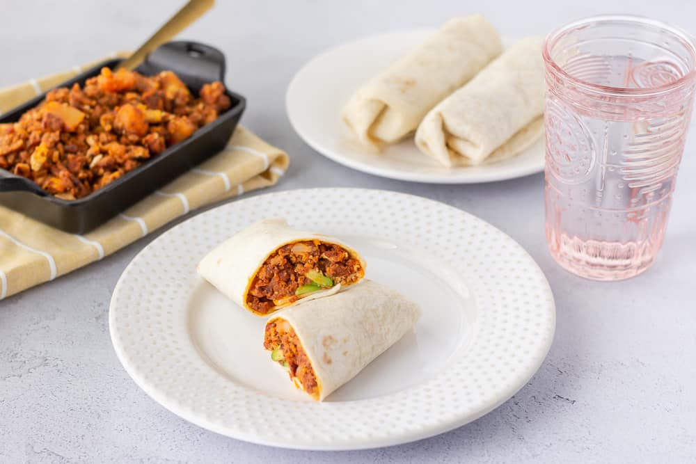 Horizontal view of burrito on a plate and a pink glass of water on the side.
