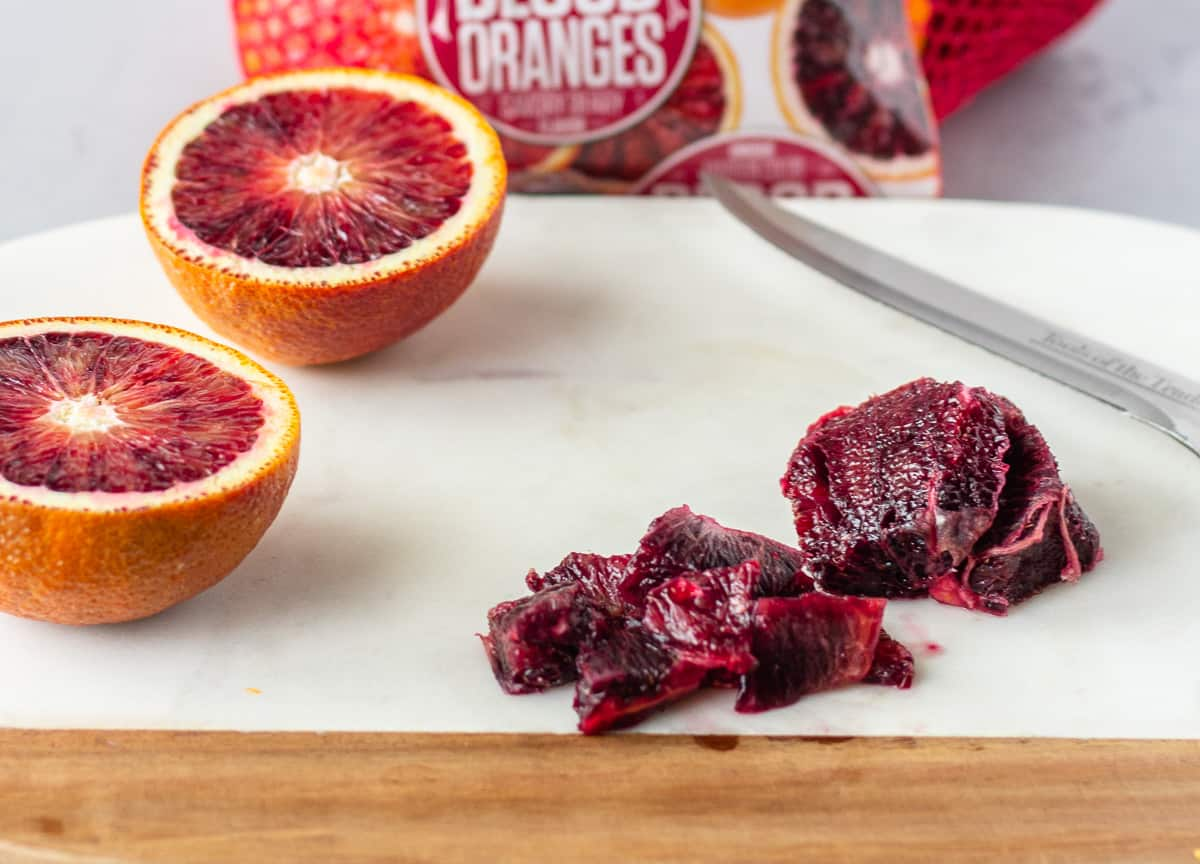 Diced blood orange and one cut in half on a marble cutting board.