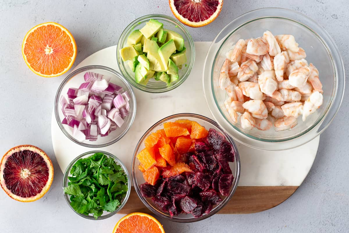 Ingredients for citrus ceviche- shrimp, diced avocado, red onion, cilantro, sliced oranges around the ingredients.