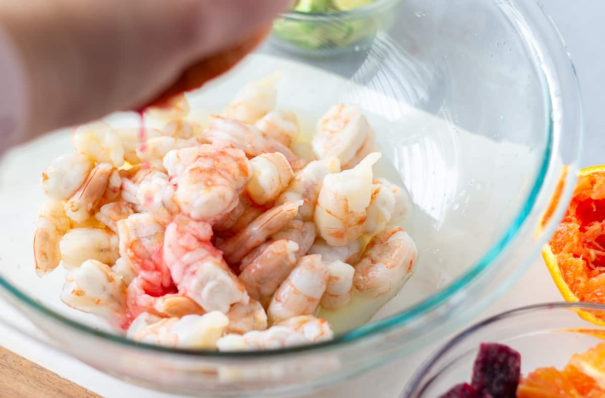Glass bowl with shrimp and hand squeezing an orange into the bowl of shrimp.