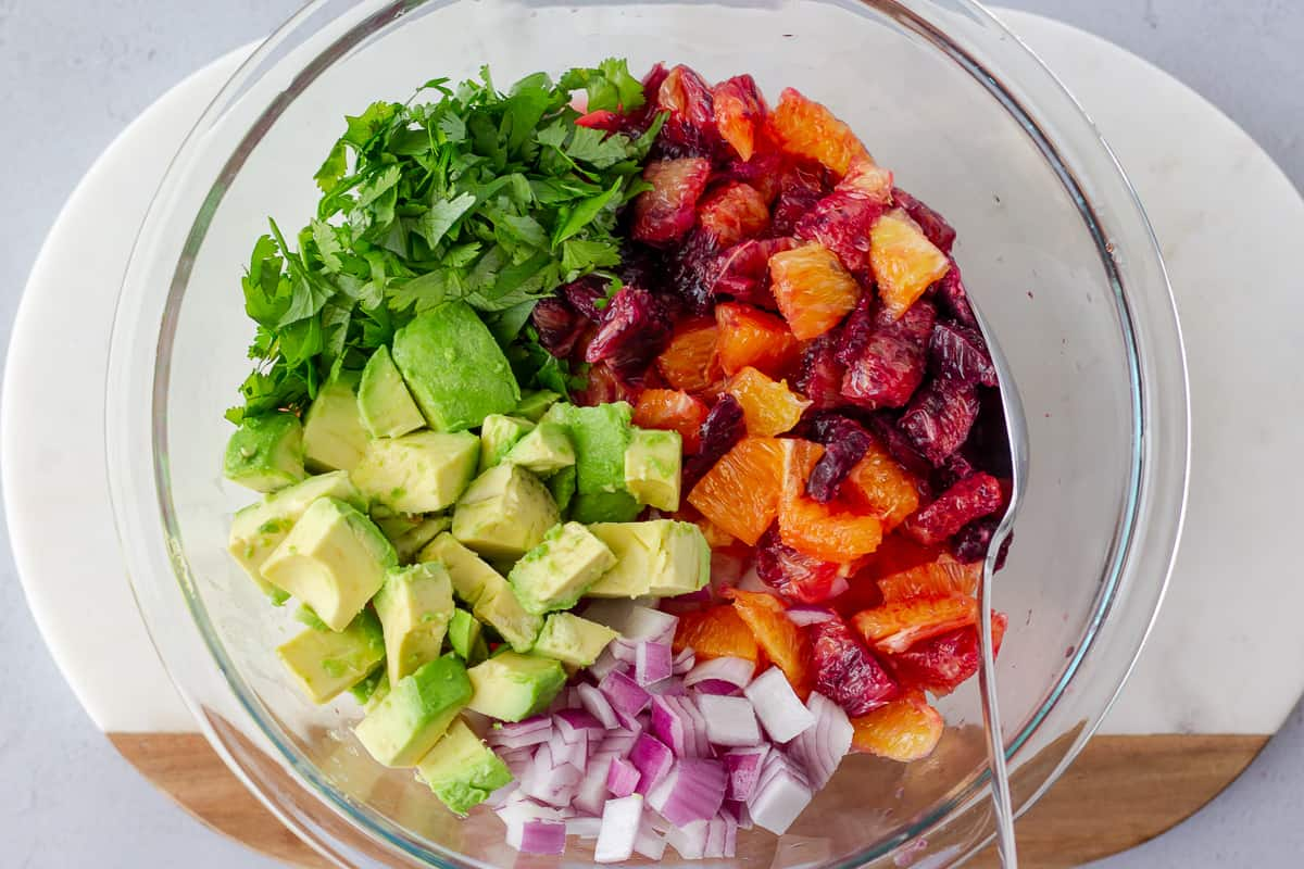 Glass bowl with diced blood oranges, oranges, red onion, avocado, and cilantro.