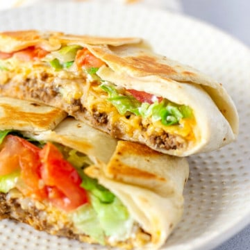 Crunch Wrap sliced in half and stacked on a plate.