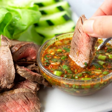 Hand holding a piece of steak being dipped into a spicy sauce.