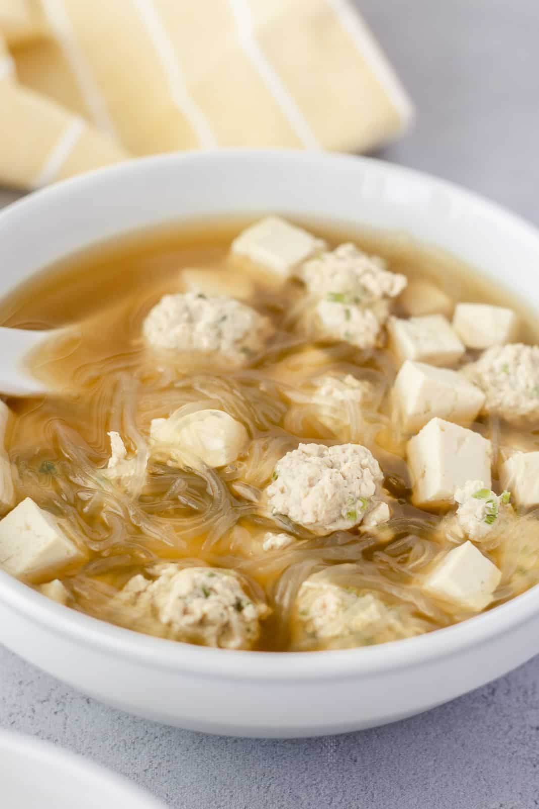 Thai glass noodle soup in a white bowl with meatballs and tofu.