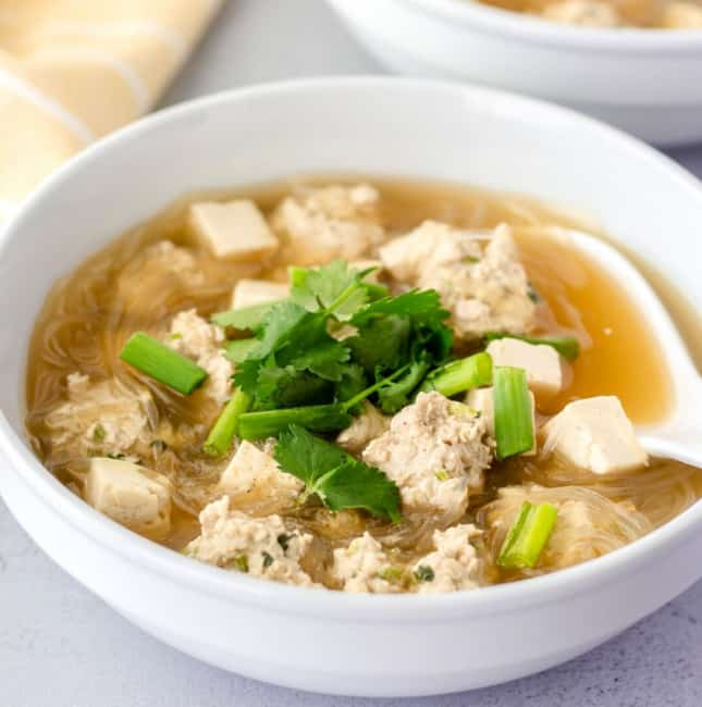 Soup in a white bowl with clean noodles, meatballs, and tofu.
