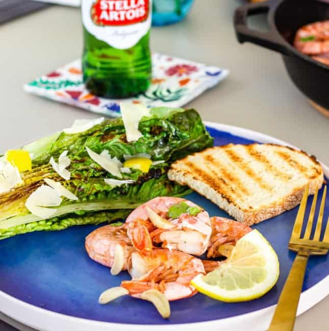 Blue plate with grilled shrimp, grilled romaine, and a slice of bread.