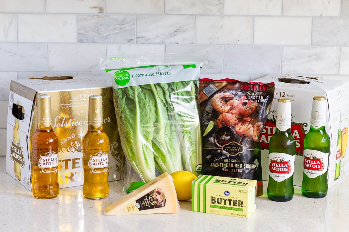 2 cases of Stella Artois Beer with bag of romaine hearts, bag or Argentinean Red Shrimp, parmesan cheese block, and butter slices.