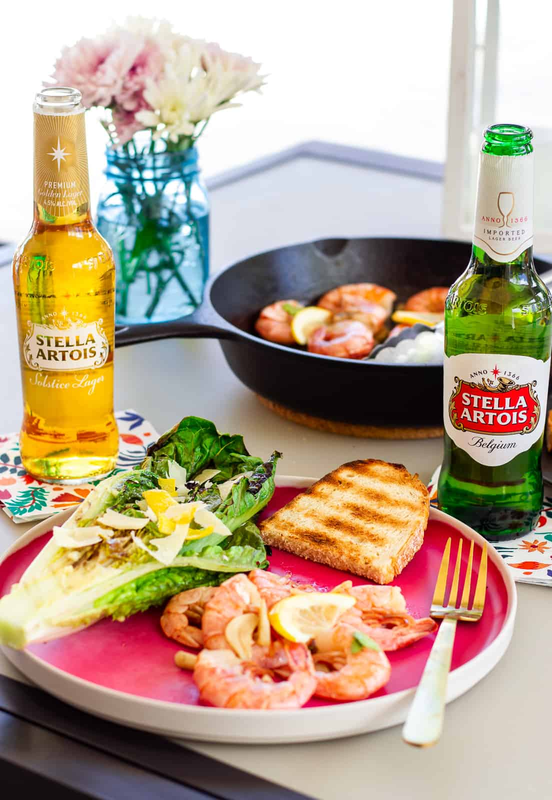 Pink plate with shrimp, slice of grilled bread, halved grilled romaine, and 2 bottles of Stella Artois Beer.