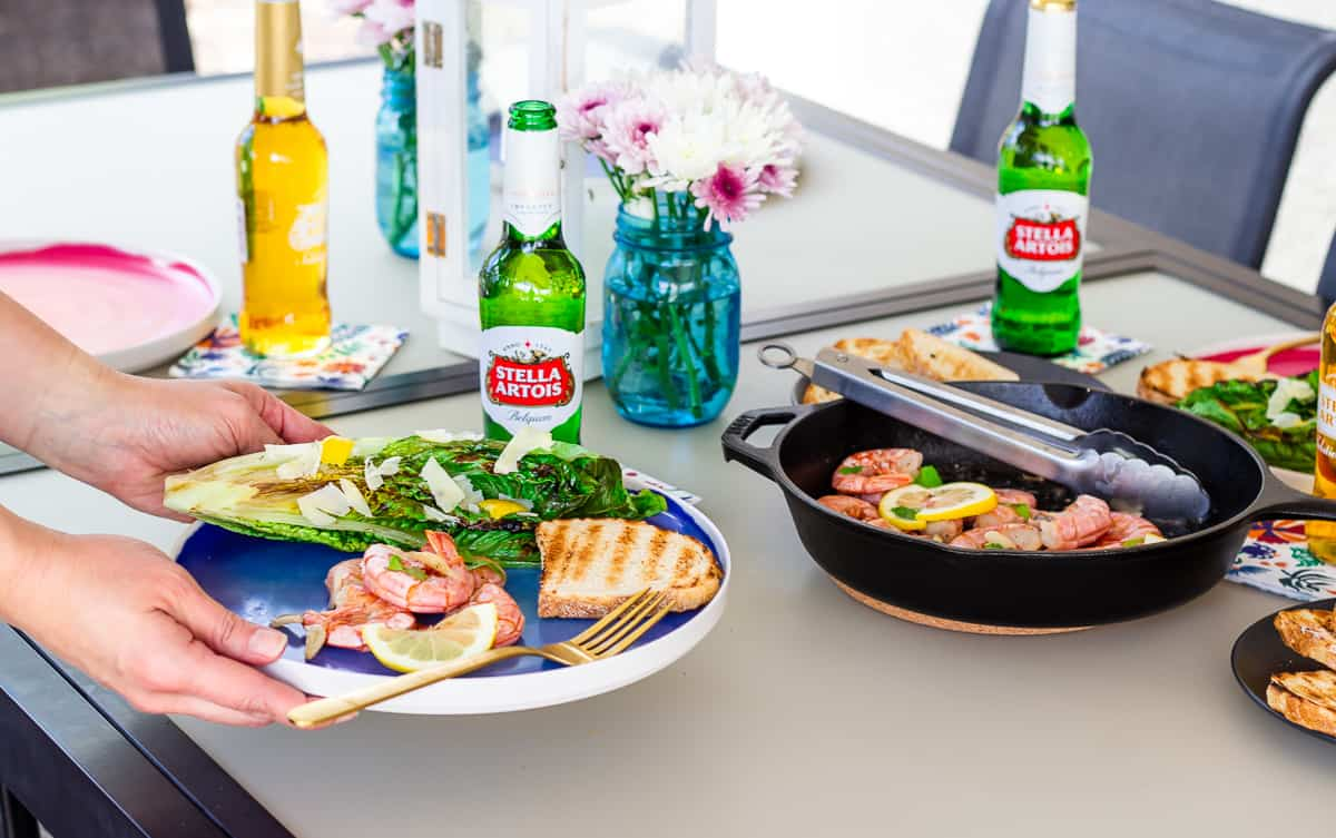 Hand holding a plate above the table with Stella Artois Beers and skillet with shrimp.