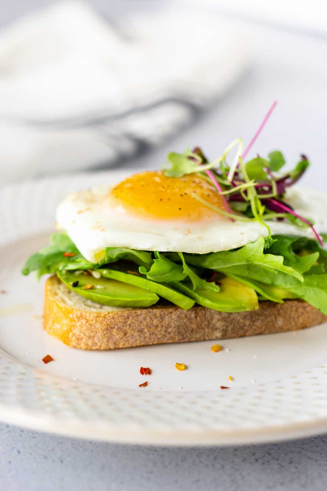 Avocado toast topped with a sunny side up egg and micro greens.