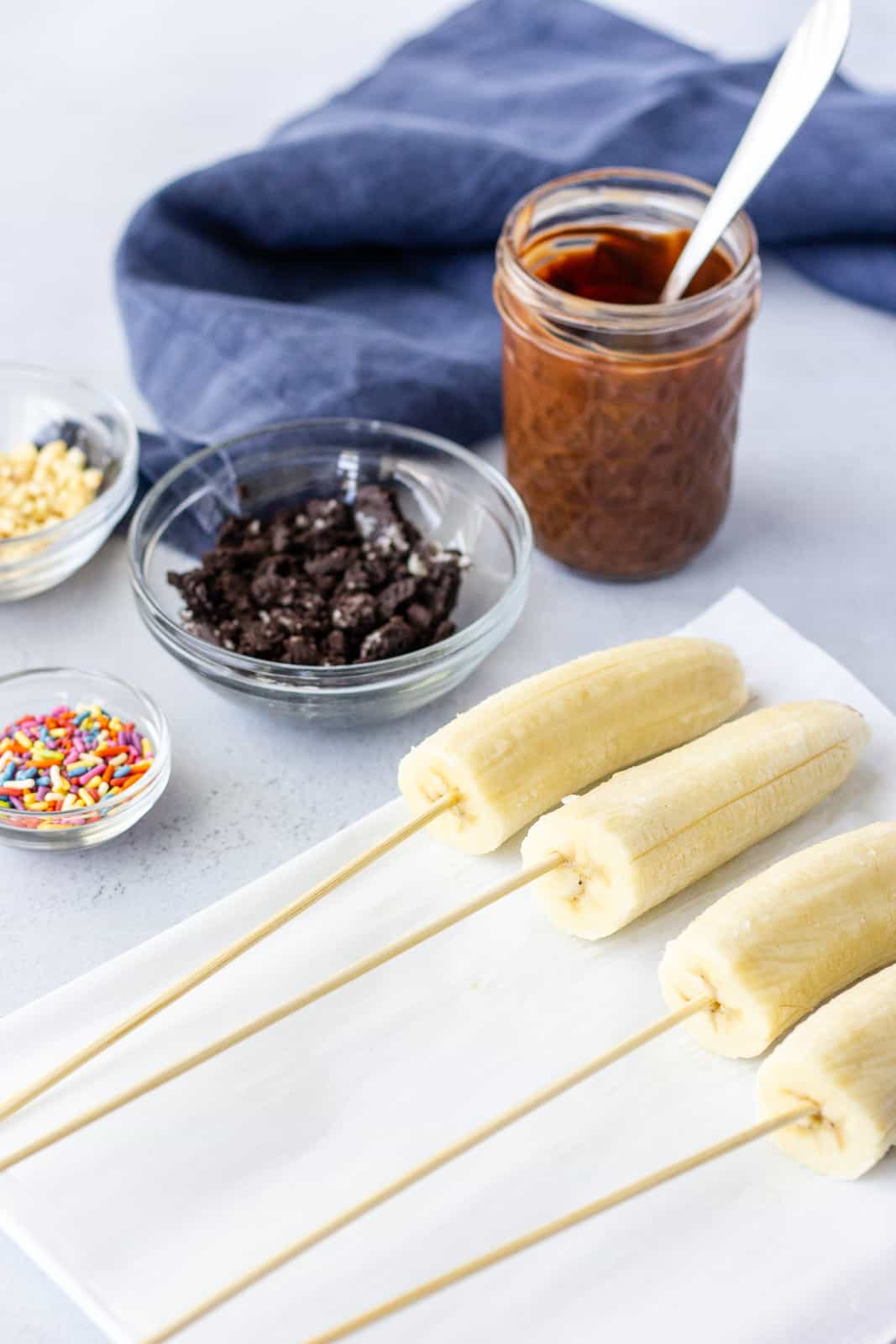 Halved bananas on skewers on a plate with a jar of melted chocolate and toppings in bowls.