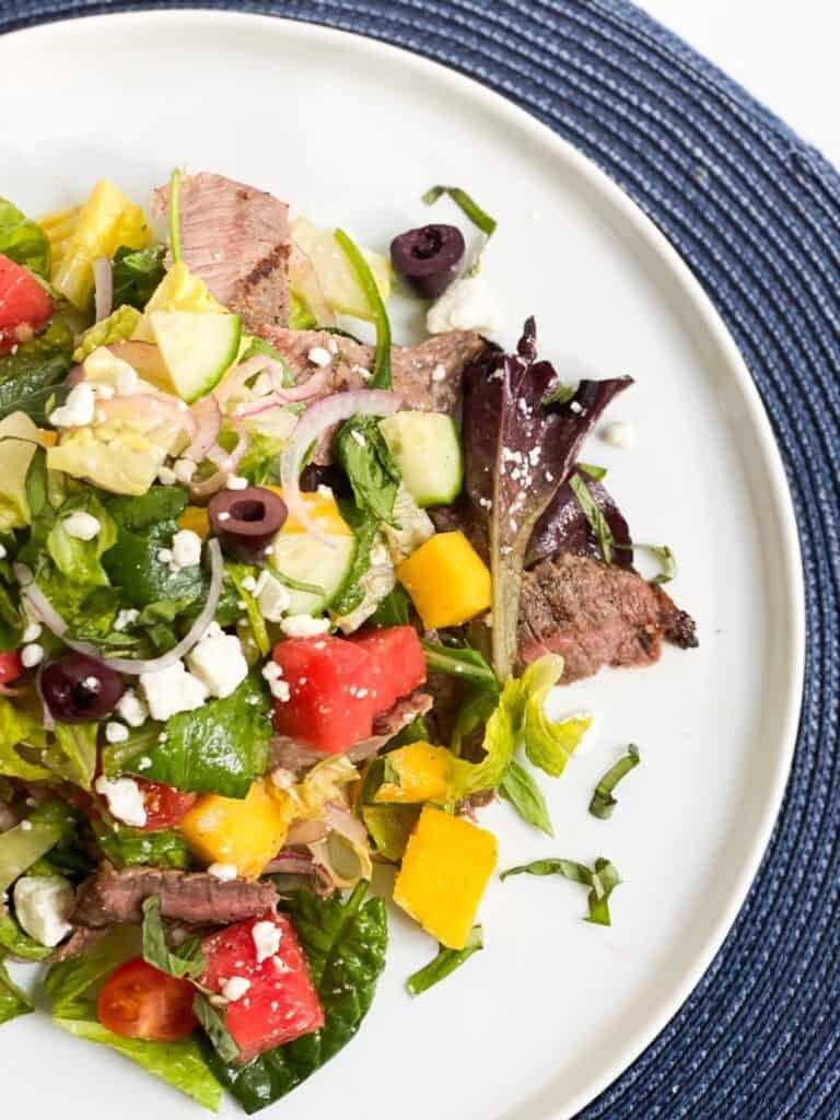 Overhead view of steak and mango salad on a white plate.