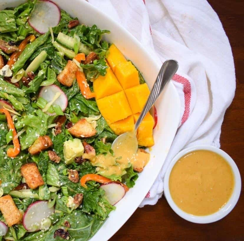 Large white bowl with salad and sliced mango on the side and a small bowl of dressing.