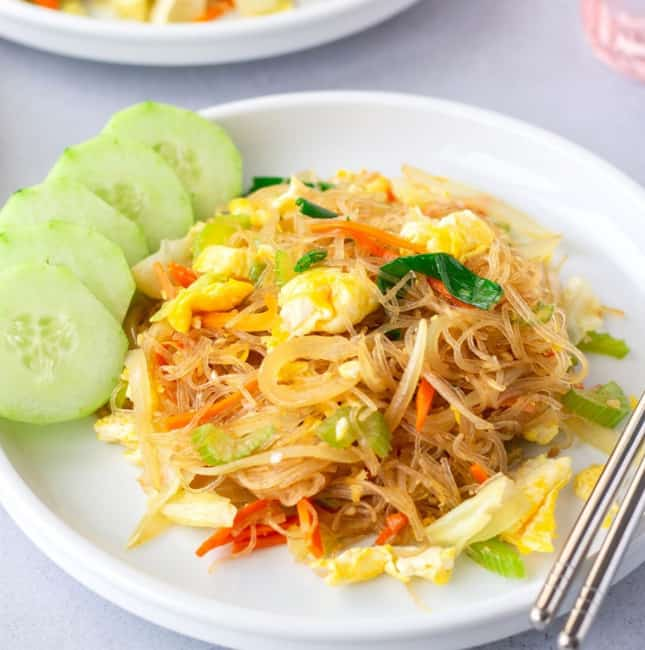 Featured image of pad woo sen on a white plate with sliced cucumbers on the side.