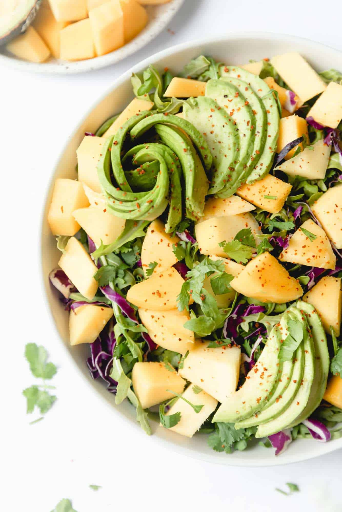 Overhead view of salad with mango chunks and avocado rose.