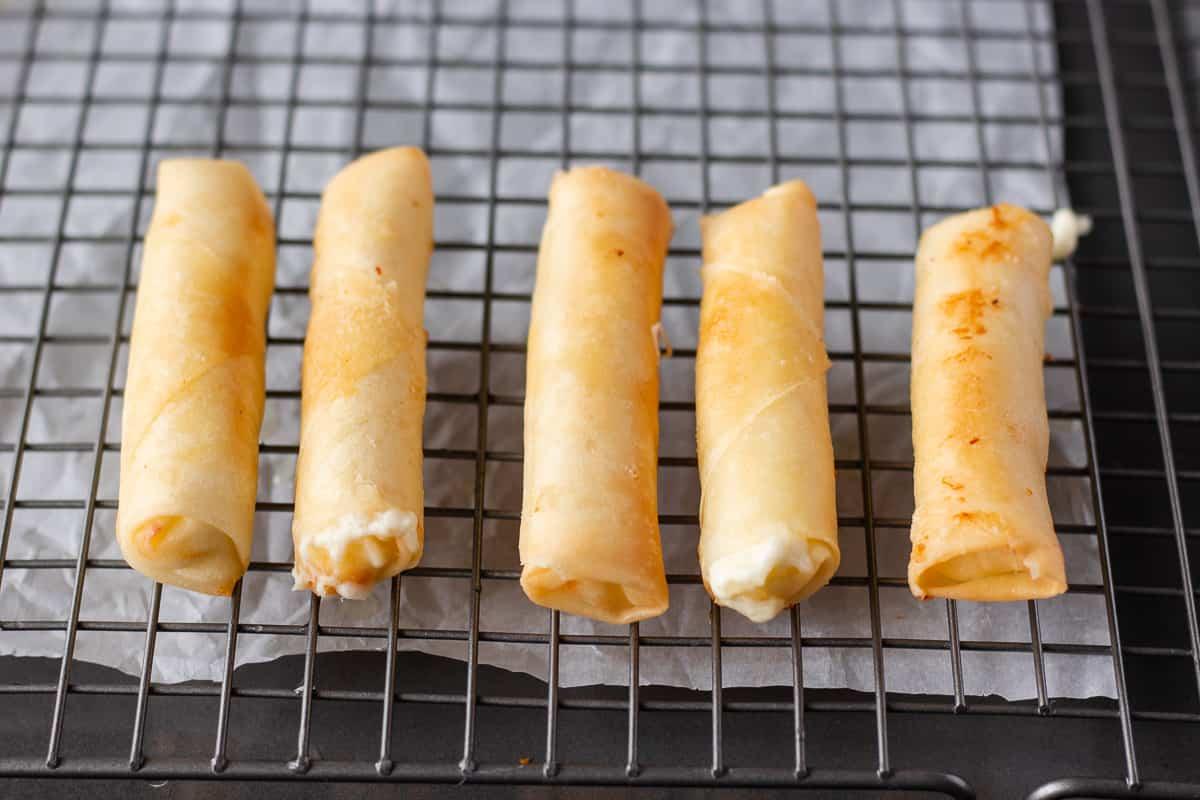 Fried Rolls on a wire baking sheet.