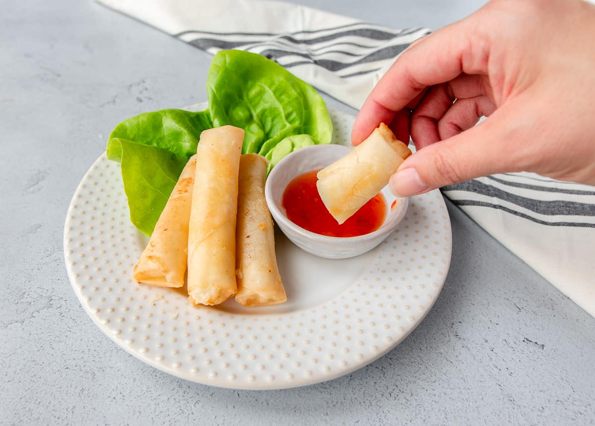 Hand holding a cheese roll being dipped into sweet chili sauce.