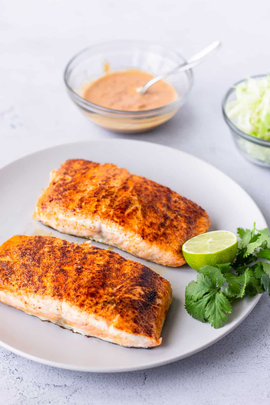 2 cooked salmon fillets garnished with lime and cilantro on the side.