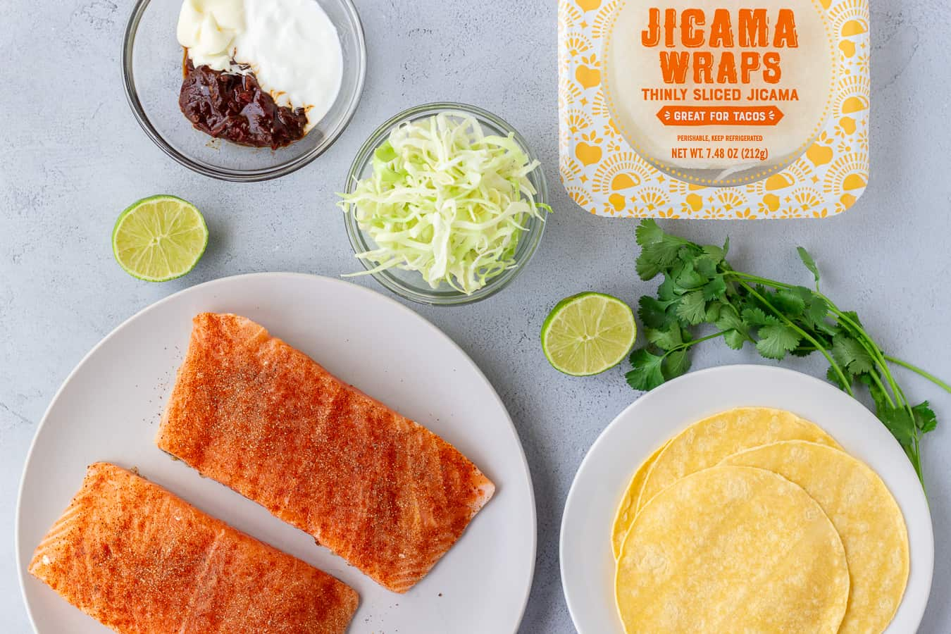 Overhead shot of ingredients, salmon fillets, shredded cabbage, corn tortillas, jicama wraps, and chipotle sauce.