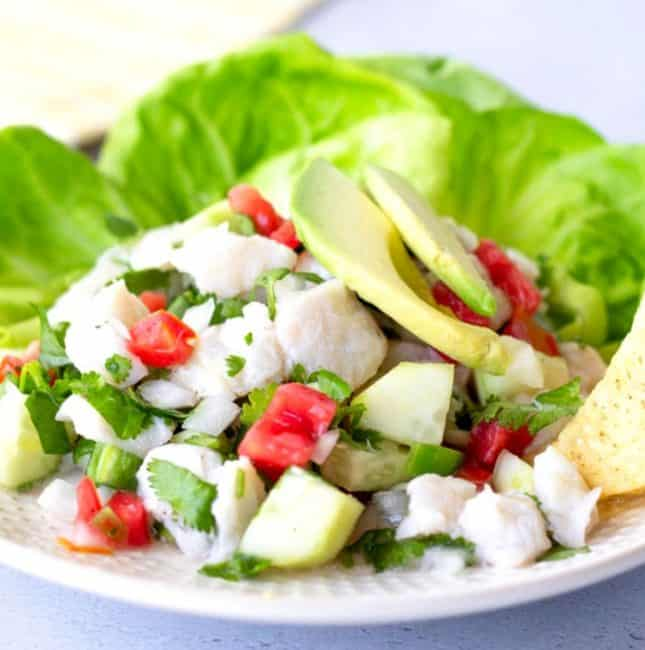Fish ceviche on a plate with lettuce leaves and topped with sliced avocado.