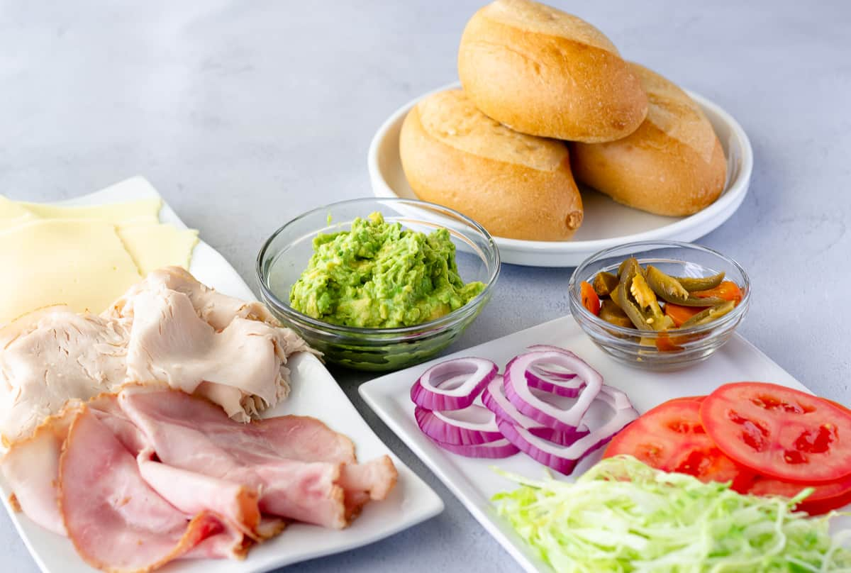 Ingredients: lunch meat, cheese, avocado, lettuce, tomato, purple onions, jalapeno, and bread rolls.