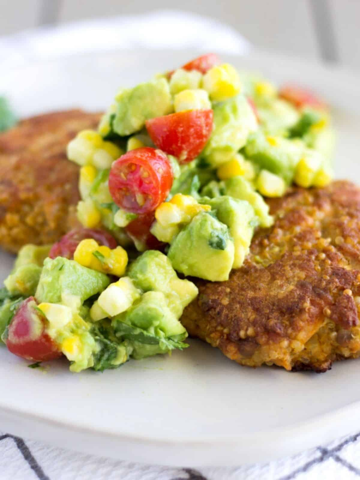 Up close view of avocado, corn, and tomato salsa on top of salmon cake.