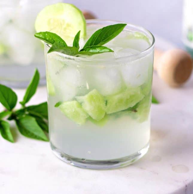 Clear glass with pieces of cucumber and garnished with basil leaves.
