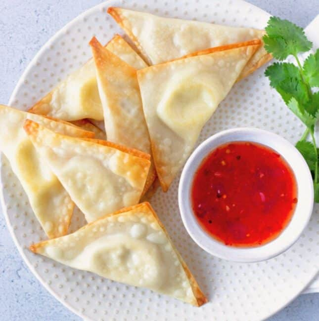 Overhead view of Cream Cheese Wontons on a round plate with a side of sweet chili sauce.