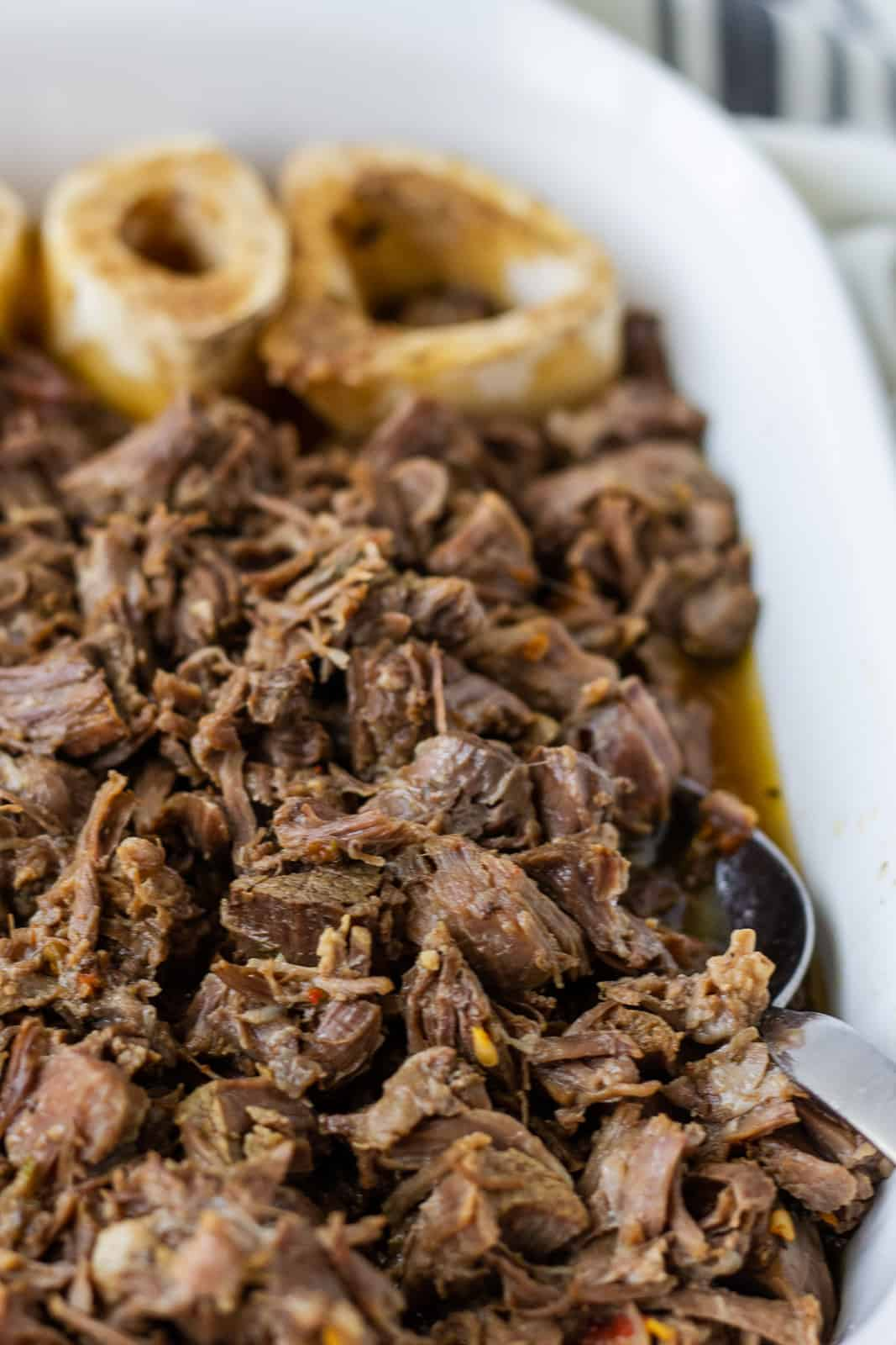 Beef bones and shredded beef in a white serving dish.