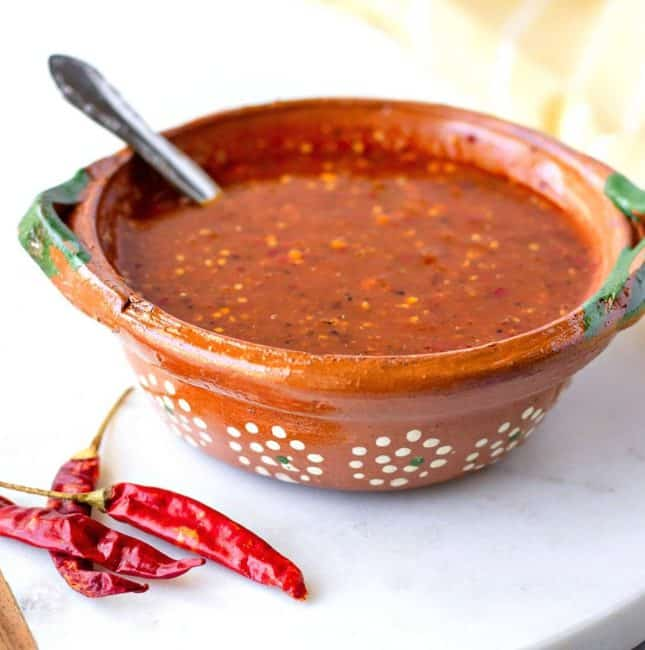Up close view of salsa in a clay bowl with chili's on the side.