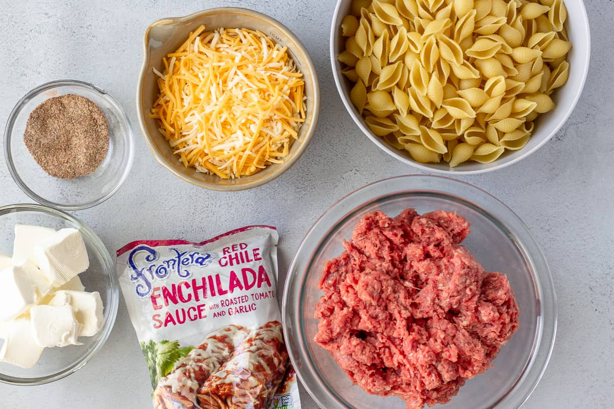 Ingredients in seperate bowls, pasta, ground beef, shredded cheese, cream cheese, and enchilada sauce.