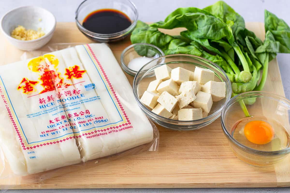 Ingredients on a cutting board, noodles, tofu, Chinese broccoli, soy sauce, and an egg.