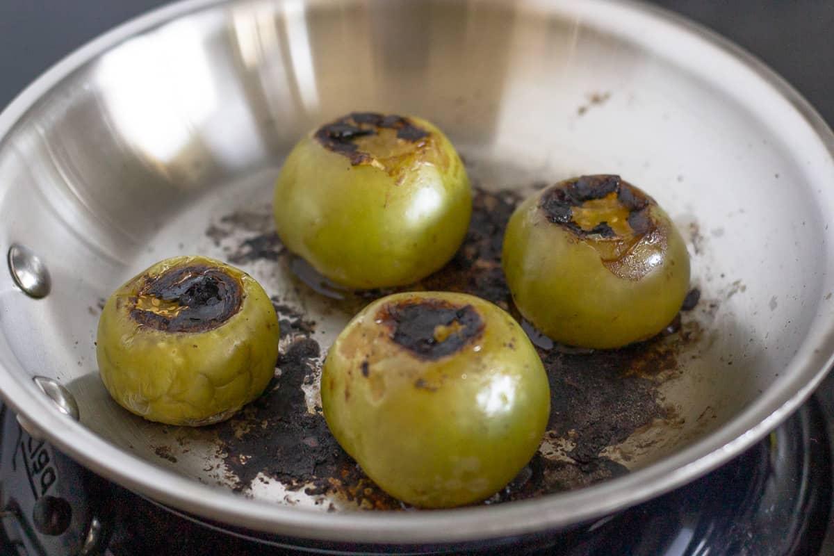 Tomatillos roasting on a pan.