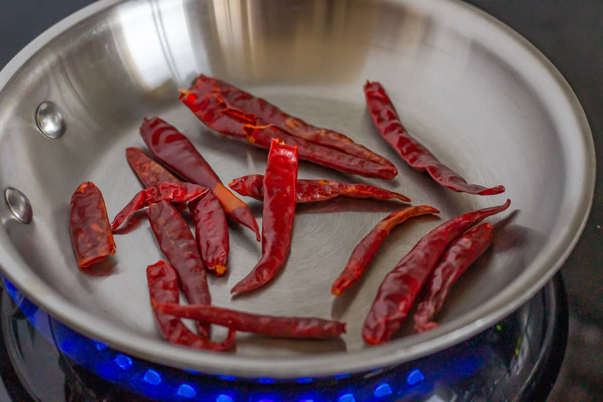 Chile's toasting in a stainless steel skillet.